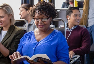 woman reading a book while riding the bus